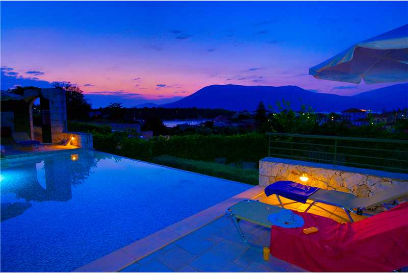 Villa DEntrolivano infinity pool illuminated at night time