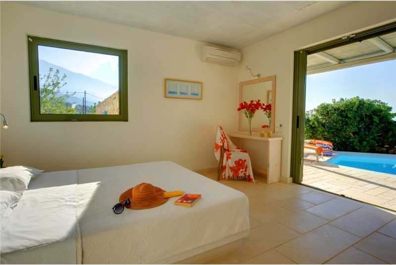 Villa Petalida master bedroom with doors leading to the pool terrace