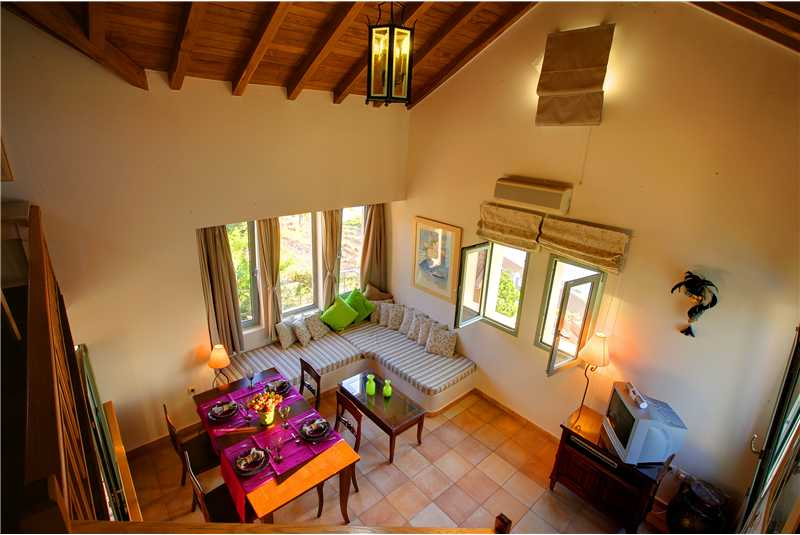 Villa Prikonas lounge and dining room with high wooden ceilings