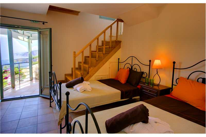 Villa Prikonas twin bedroom with stairs leading up to the kitchen